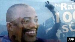Hình ảnh những người ủng hộ Tổng thống Kabila phản chiếu trên tấm áp phích hình ông sau khi kết quả bầu cử được công bố tại thủ đô Kinshasa, Cộng hòa Dân chủ Congo, 9/12/2011