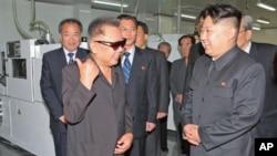 Kim Jong Il à esquerda falando com o seu filho e sucessor Kim Jong-un