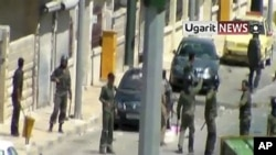 Image made from amateur video released by Ugarit News and accessed via AP TV News on Aug. 8, 2011, shows members of the Syrian military standing near the body of man in the northern Syrian province of Idlib Sunday Aug. 7, 2011. (Contents and date cannot b