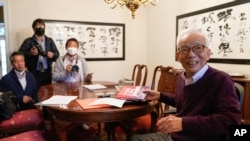 Syukuro Manabe, right, speaks to reporters at his home in Princeton, N.J., Tuesday, Oct. 5, 2021. (AP Photo/Seth Wenig)