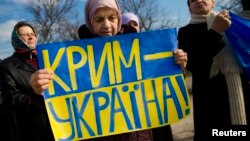 "FILE - An ethnic Tatar women attends a rally denouncing a referendum which Moscow used to legitimize its annexation of Ukraine's Crimea, in Simferopol, March 14, 2014. The sign reads ""Crimea is Ukraine."