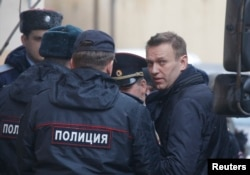Russian opposition leader Alexei Navalny is escorted upon his arrival for a hearing after being detained at the protest against corruption, at the Tverskoi court in Moscow, Russia, March 27, 2017.