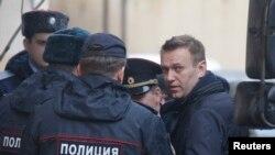 Le leader de l'opposition russe Alexei Navalny est flanqué par des policiers lors de son arrivée au tribunal de Tverskoi, à Moscou, Russie, 27 mars 2017.