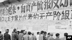 Passersby stop to read posters plastered on the wall in Peking where the Red Guard demonstrators are carrying on their cultural revolution, November 1, 1967.