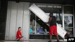 Jason Brock (L) và Kevin Hunter lắp cửa chớp chống bão phía trước của một cơ sở kinh doanh trong lúc bão Matthew đang trên đường đổ bộ, Delray Beach, Hoa Kỳ, ngày 06 tháng 10 năm 2016.