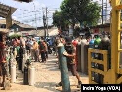 Seorang pegawai toko pengisian ulang tabung oksigen di Manggarai, Jakarta Selatan, membawa tabung oksigen medis yang baru tiba dari produsen, Senin, 5 Juli 2021. (Foto: Indra Yoga/VOA)