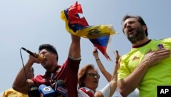 FILE - Chacao Mayor Ramon Muchacho, right, and Venezuelan singer Jesus Alberto Miranda, known as Chino, sing the national anthem during an anti-government protest in Caracas, Venezuela. Venezuela's high court ordered the removal and arrest of Muchacho Aug. 8, 2017, for not following an order to remove barricades set up in his district of Caracas.