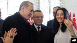 Turkey's President Recep Tayyip Erdogan, left, poses for a selfie photo with Imane Elbani, right, at his palace before addressing a group of farmers, in Ankara, Turkey, Monday, Nov. 14, 2016.