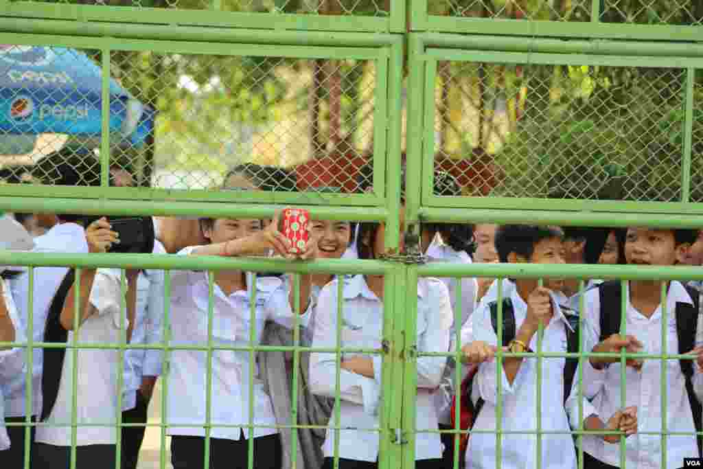 High school students peek through a school gate to cheer and take pictures of a protest in Phnom Penh, Oct. 25, 2013. (Heng Reaksmey/VOA Khmer)