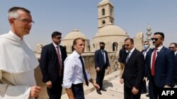 French President Emmanuel Macron (C) tours the Our Lady of the Hour Church with Dominican Father Olivier Poquillon (L) in Iraq's second city of Mosul, in the northern Nineveh province, on August 29, 2021.