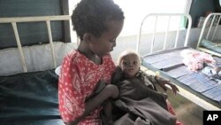 Abdi Nur Ibrahim, 1, who is being treated for severe malnutrition, is cared for by his older sister at a Doctors Without Borders hospital in Dagahaley Camp, outside Dadaab, Kenya, July 15, 2011