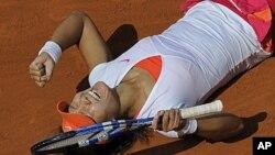 ນາງ Li Na ແຫ່ງຈີນ ດີໃຈທີ່ເປັນເເຊັມໃໝ່ໃນການແຂ່ງຂັນ ກີລາເທັນນີສ French Open ໂດຍໄດ້ຊະນະນາງ Francesca Schiavone ແຊັມປີກາຍນີ້ ຈາກອີຕາລີ, ທີ່ກຸງປາຣີ ວັນທີ 4 ມິຖຸນາ 2011.
