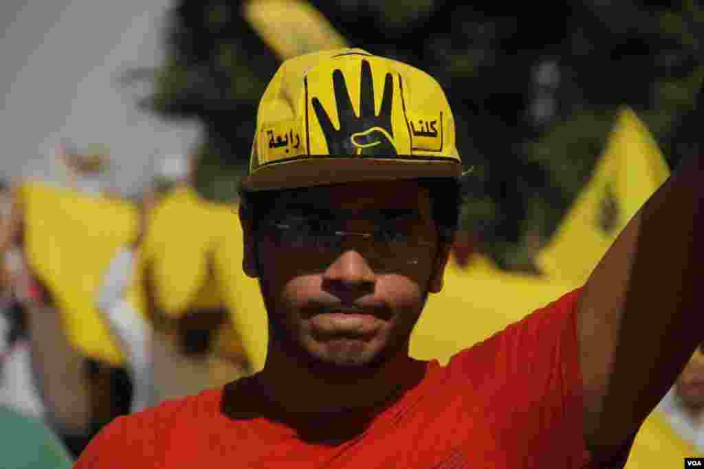 A protester wears a hat with the image of a hand holding up four fingers, Maadi, southern Cairo, Sept. 20, 2013. (Hamada Elrasam for VOA)