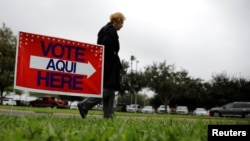 FILE - A woman arrives at a polling station in Lark Community Center as early voting for midterm elections started, in McAllen, Texas, Oct. 22, 2018.