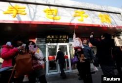 """2013年12月29日,人们在北京庆丰包子铺门前拍照留念。前一天,中国国家主席习近平在庆丰包子铺用餐。后来有些不满习近平的人称他为""""习包子""""""""庆丰帝""""。"""