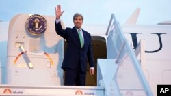 FILE - Secretary of State John Kerry waves as he boards his plane at Orly Airport, south of Paris, France, en route to Vienna, Austria, Oct. 15, 2014.