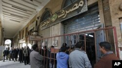 Libyan citizens queue outside a bank to get cash, in Benghazi, Libya