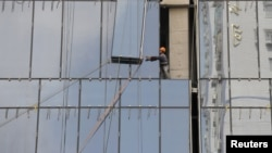 A laborer installs a glass wall on a commercial building under construction in Nanjing, Jiangsu province, China, August 6, 2012.