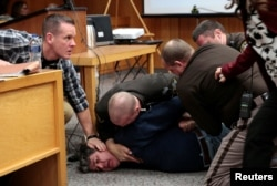 Eaton County sheriffs restrain Randall Margraves after he lunged at Larry Nassar, a former team USA Gymnastics doctor who pleaded guilty in November 2017 to sexual assault charges, during victim statements of his sentencing in the Eaton County Circuit Court in Charlotte, Michigan, Feb. 2, 2018.