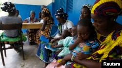 FILE - Women holding children wait for a medical examination at the health center in Gbangbegouine, Ivory Coast.