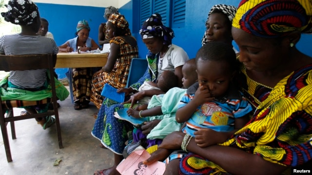 FILE - Women holding children wait for a medical examination at the health center in Gbangbegouine, Ivory Coast