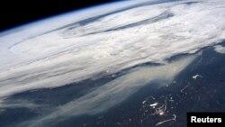Kolom asap (bawah) dari kebakaran lahan di dan sekitar Ft McMurray, Alberta, Kanada, terlihat dalam foto yang diabadikan oleh astronot NASA, Jeff Williams, dari Stasiun Luar Angkasa Internasional, 11 Mei 2016.