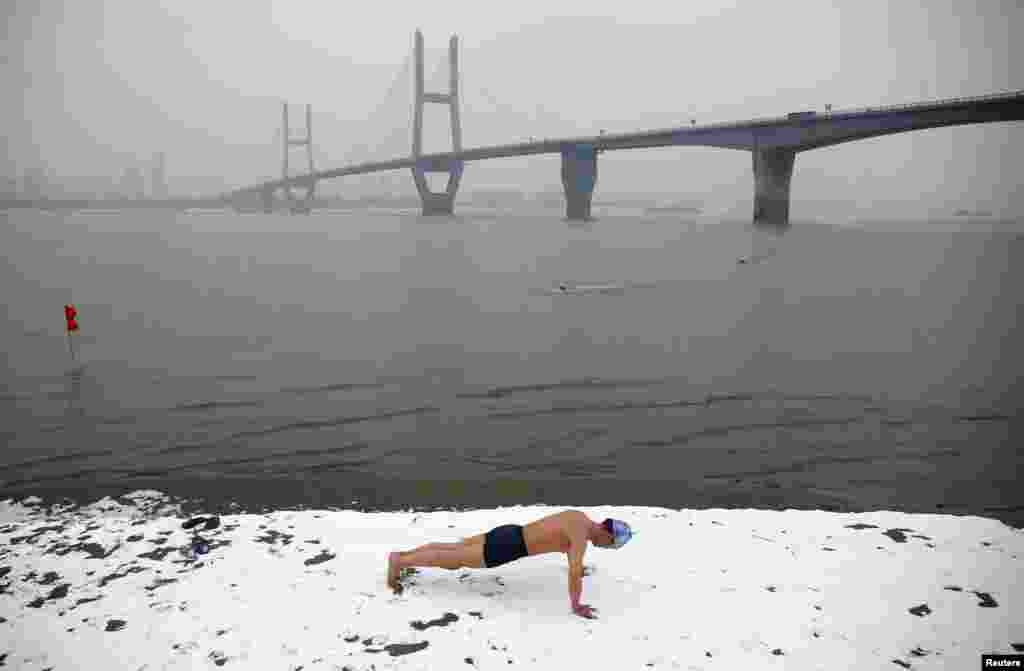 A winter swimmer does push-ups on the snow-covered banks of the Yangtze River in Wuhan, Hubei province, China.