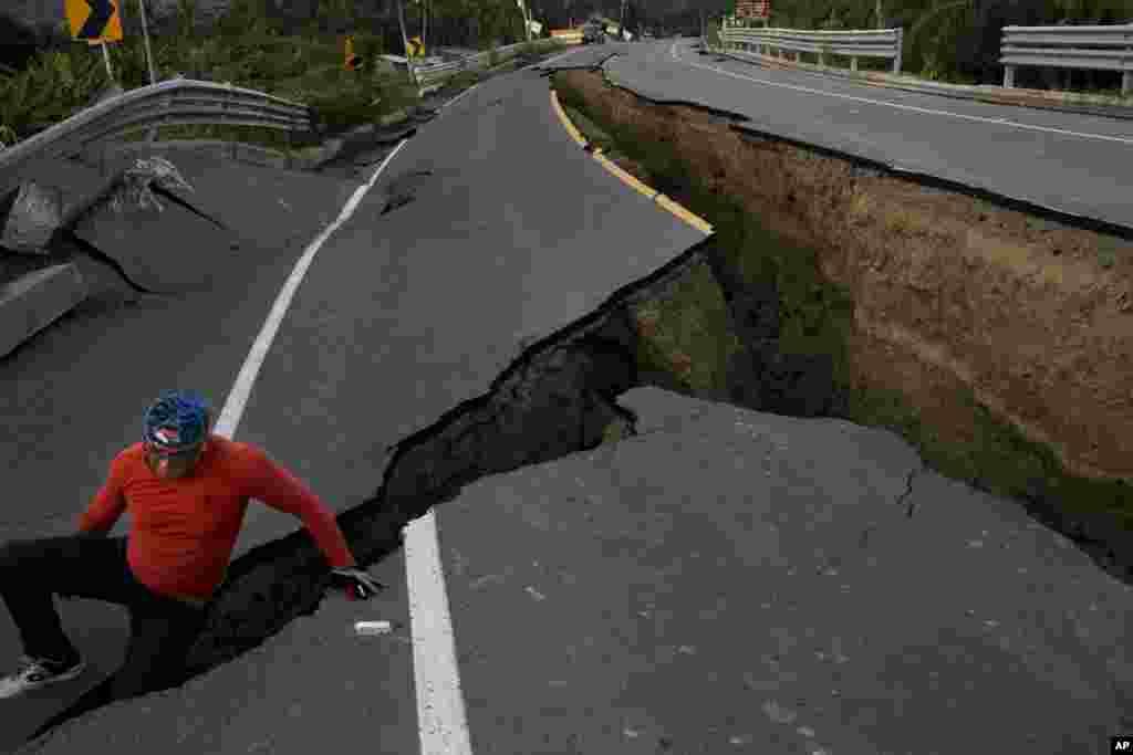 Seorang pria berpose di sebuah jalan yang rusak akibat gempa berkekuatan 7,8 skala Richter di kota Chacras, Ekuador.