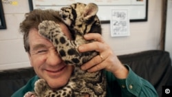 Joel Sartore and a clouded leopard cub cuddle after a photo shoot at the Columbus Zoo in Ohio. The leopards, which live in Asian tropical forests, are illegally hunted for their spotted pelts. (Photo by Grahm S. Jones/National Geographic Photo Ark)