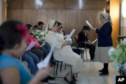 FILE - Migrants participate in a Three Kings Day Mass at the Casa del Migrante shelter run by Catholic nuns in Reynosa, Mexico, Jan. 6, 2016.