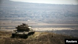 The Syrian area of Quneitra is seen in the background as an out-of-commission Israeli tank parks on a hill, near the ceasefire line between Israel and Syria, in the Israeli-occupied Golan Heights, Aug. 21, 2015.