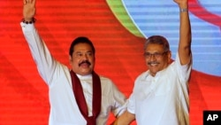 Former Sri Lankan president Mahinda Rajapaksa, left, and former Defense Secretary and his brother Gotabaya Rajapaksa wave to supporters during a party convention held to announce the presidential candidacy in Colombo, Sri Lanka, Sunday, Aug. 11, 2019. (AP