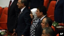 A group of ruling party lawmakers look on as newly elected legislators take their oaths during the new Turkish parliament's opening session in Ankara, Turkey, June 23, 2015.