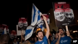 FILE - Israelis hold up banners during a demonstration in Tel Aviv against the emerging natural gas deal, Nov. 28, 2015.