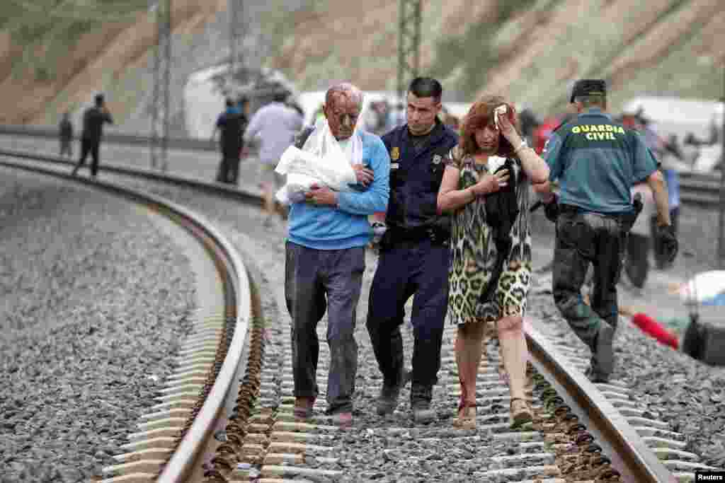 Victims are helped by rescue workers after a train crashed near Santiago de Compostela, Spain, July 24, 2013.