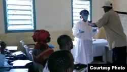A Red Cross volunteer helps the CDC's Paulyne Ngalame Ntuba put on personal protective equipment, typically worn by burial teams, in Forecariah, Guinea, on October 5, 2014. (Photo courtesy of Centers for Disease Control and Prevention)