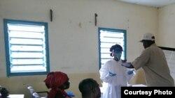 Un volontaire de la Croix-Rouge guinéenne aidant un volontaire à se protéger contre le virus à Ebola (Photo CDC)