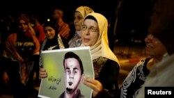Ibu Bilal Kayed, seorang Palestina yang mogok makan, memegang fotonya saat melakukan protes menuntut pembebasannya di Barzilai Hospital kota kota Ashkelon, Israel selatan, 9 Agustus 2016 (REUTERS/Amir Cohen)