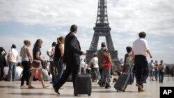 Turis dan pengusaha di alun-alun Trocadero di depan Menara Eiffel.