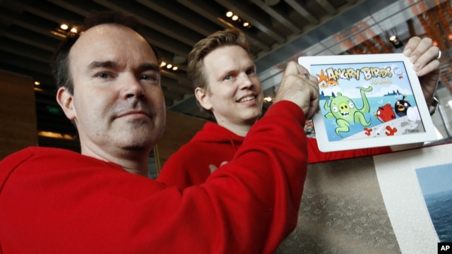 Peter Vesterbacka, direktur pemasaran perusahaan Mighty Eagle (kiri) dan Henri Holm, wakil presiden senior Rovio Asia, menunjukkan versi terbaru permainan Angry Birds pada pembukaan kantor cabang Rovio, yang memproduksi permainan tersebut, di Shanghai. (AP/Eugene Hoshiko)
