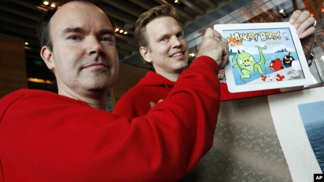 Peter Vesterbacka, Mighty Eagle, Chief Marketing Officer, left, and Henri Holm, Senior Vice President Of Rovio Asia, right, show the latest version of Angry Birds after the opening ceremony of the Shanghai office of Rovio, maker of popular computer game.