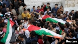 Palestinians carry the bodies of Amer Nassar, 17, and Naji Belbisi, 18, into a mosque during their funeral in the West Bank, April 4, 2013.