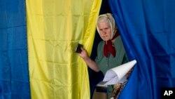 Seorang perempuan keluar dari bilik setelah memberikan suaranya dalam pemilihan presiden di Krasnoarmiisk timur, Ukraina, Minggu, 25 Mei 2014.