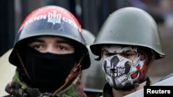 Manifestantes antigubernamentales vigilan una barricada en Kiev. El gobierno y los manifestantes parecen haber llegado a un acuerdo.