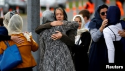 People embrace as they attend the burial ceremony of the victims of the mosque attacks, at the Memorial Park Cemetery in Christchurch, New Zealand, March 21, 2019.