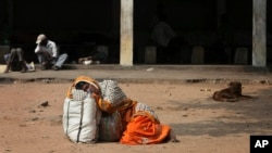 FILE - An Indian attendant of a patient suspected with swine flu virus rests on the ground in the premises of Gandhi Hospital in Hyderabad, India, Wednesday, Jan. 21, 2015. According to local reports, nine people died of the flu at the state-run hospital.