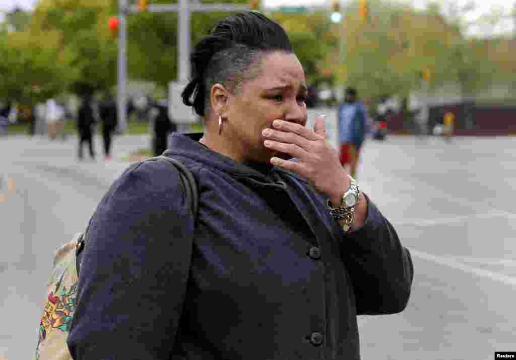 A woman cries as demonstrators throw rocks at Baltimore police during clashes in Baltimore, Maryland, April 27, 2015.