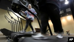 Gym members use as treadmill to warm up for a morning exercise class at Downsize Fitness, in Addison, Texas, Jan. 3, 2013.