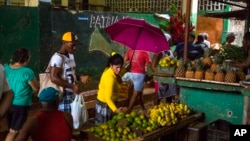 FILE - People shop at the El Egido food market in Havana, Cuba, Dec. 4, 2015.