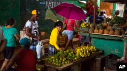 FILE - People shop at the El Egido food market in Havana, Cuba. Cuban state-run media reported on April 13, 2016 that Cuba will open its state-controlled wholesale market to a limited number of private business owners in response to rising food prices that may have angered many ordinary Cubans.